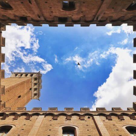 blick auf blauen himmel durch mittelalterliche mauern eines innenhofes