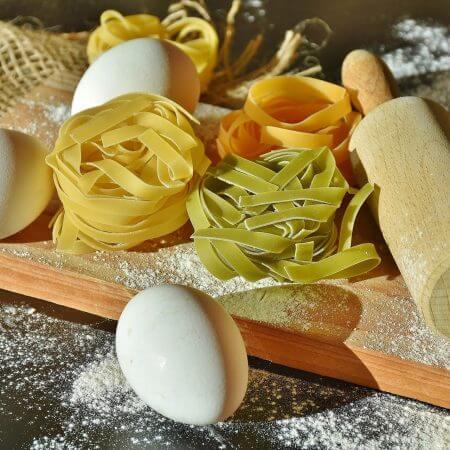 bandnudeln eier und nudelwalker auf tisch