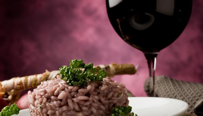 teller mit rotem risottoreis und einem glas rotwein