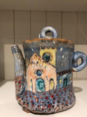 handgemachte blaue teekanne mit bunten motiven